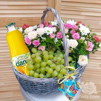 Виноград, цветы и напиток в плетеной корзине